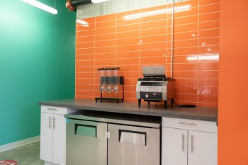 Breakfast area with cereal dispenser and toaster with orange and green walls.