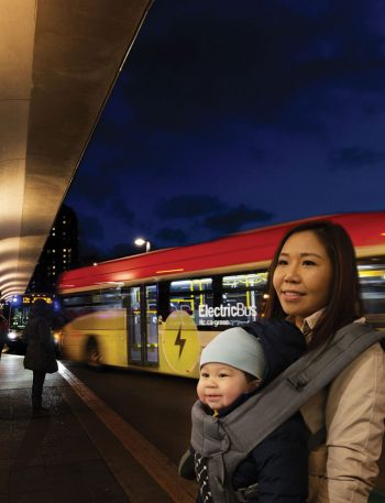 A woman holding a baby in a baby sling stands in front of a bus on a boarding platform at night.