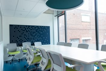 Large white table with 7 office chairs and large window.