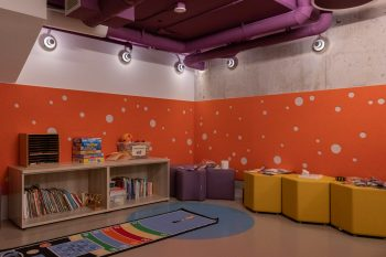 orange children's play area with toys and matts