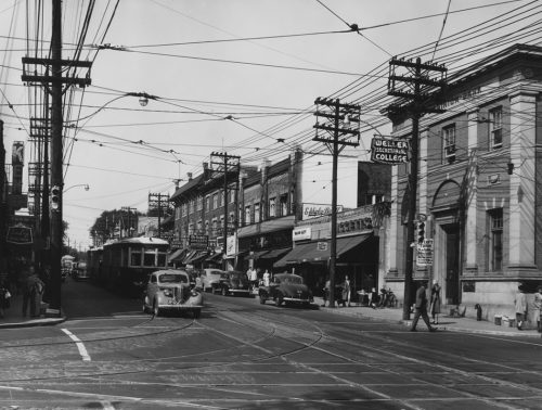 A busy street with cars and a streetcar. Lining the street are stores and services, including Weller Secretarial College.