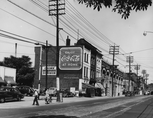 """A parking lot with a row of stores behind it, and a billboard that reads, """"Enjoy Coca-Cola at home."""""""