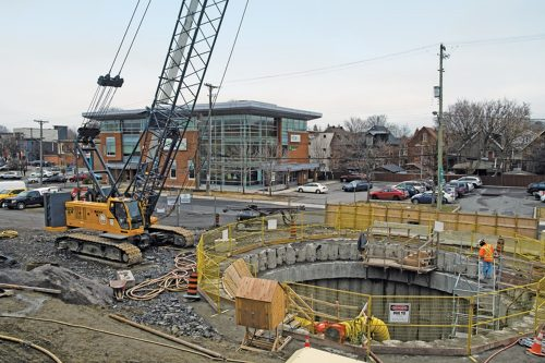 Photo of a large open circular shaft is surrounded by construction equipment