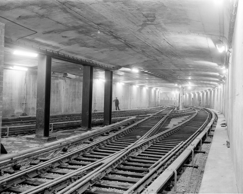 A square concrete tunnel with overlapping sets of tracks.