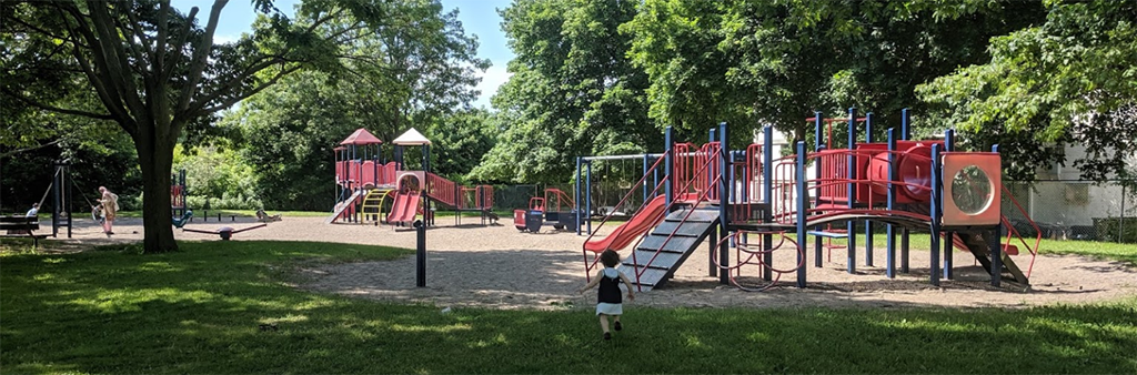 The playground in Byng Park on a sunny day which includes two separate play structures shown in red and blue on top of sand and surrounded by mature trees and grass.