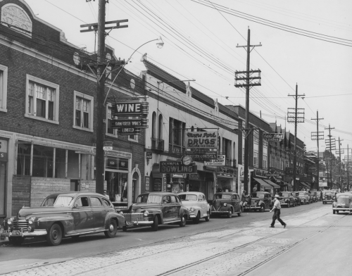 A row of brick stores and services, including Danforth Wines, Olympia Bowling, Moore Park Drugs, and Eddie Black Radio.