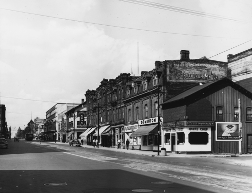 A street of three-storey brick stores, including a Dominion grocery store and the White Chef restaurant.