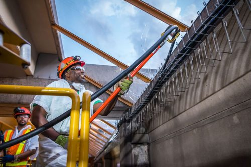 A Black man in a hardhat guides a thick cable onto hooks.