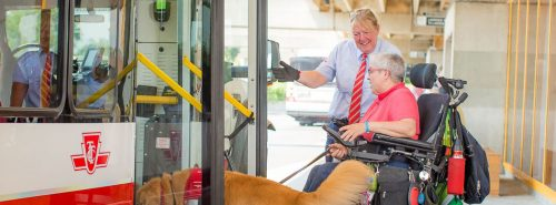 A man sits in a wheelchair and holds the leash of a golden retriever dog. A smiling TTC driver gestures at him to enter to open bus doors.