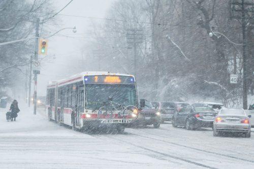 A TTC bus drives through a thick snowfall.