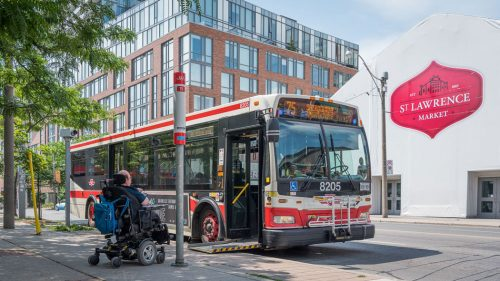 A man in a wheelchair sits in front of a ramp leading onto a TTC bus. Behind the bus is a sign for the St. Lawrence Market.