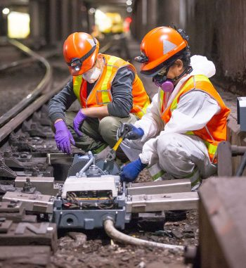 People in hardhats and protective masks weld electronic components together in a subway tunnel.
