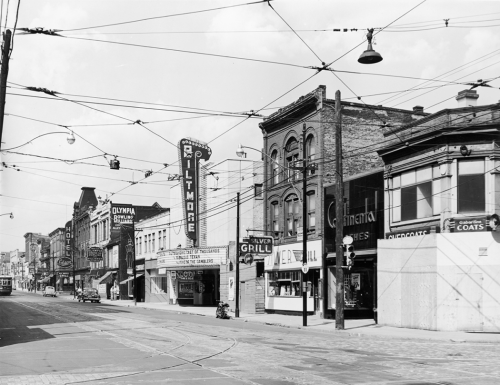 A line of stores and services include the Silver Grill, the Biltmore cinema, Continental Clothes, and a boarded-up building on the corner.