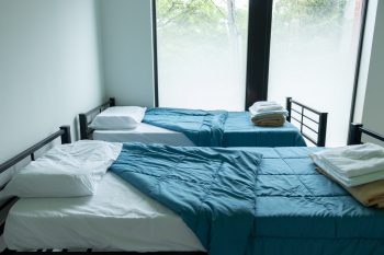 Two beds with blue covers and a large window.