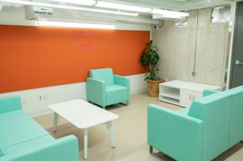 orange walls with three teal couches.