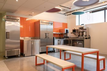 orange kitchen with industrial fridge and white picnic table
