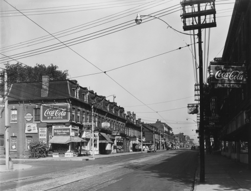 A row of identical three-storey brick stores. On the corner is a store with awnings over the entrance and a large Coca-Cola sign on the side.