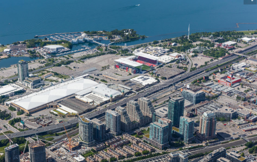 Exhibition Place grounds seen from above, looking south west toward Lake Ontario. The image shows large, flat exhibition buildings, parking lots and roads, surrounded by the highway and rail corridor to the north