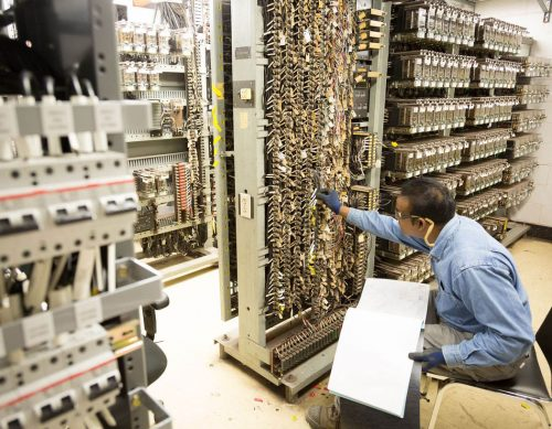 A man checks electronic equipment in a tall rack.