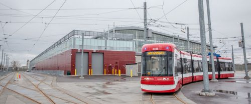 A long red streetcar stands in front of a modern brick and glass building in the rain.