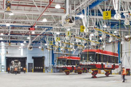 Two TTC buses are held off the ground by jacks and ropes in a large white garage.