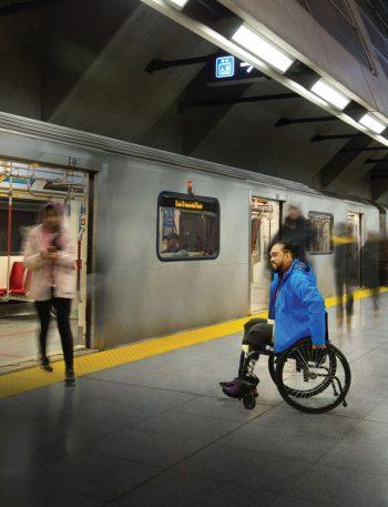 A man in a wheelchair waits to board a subway train.