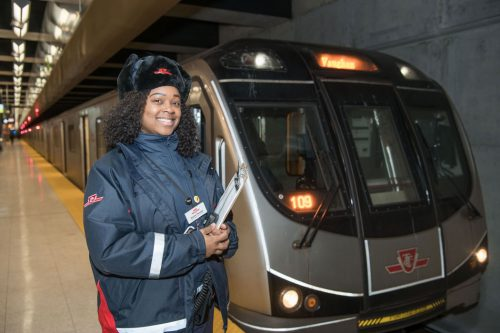 A smiling Black woman in a TTC coat and winter hat stands beside a subway train.