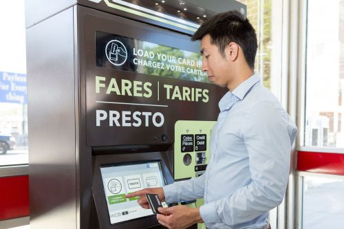 An Asian man uses a touchscreen on a ticket machine.