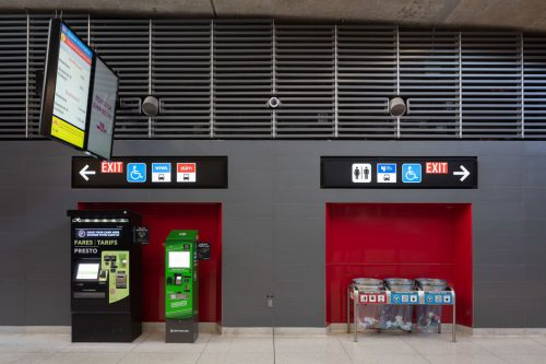 In a subway station , a digital screen and signs on the wall direct people to subway lines, elevators and exits.