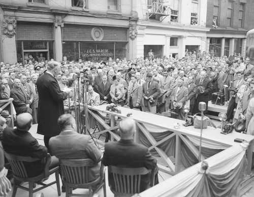 A man stands at a microphone on a platform set up on the street. Other people are sitting behind him, and there is a crowd in front of the platform.