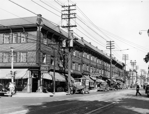 A long three-storey building containing many stores. A Brown's Bread delivery wagon pulled by a horse is parked at the curb.