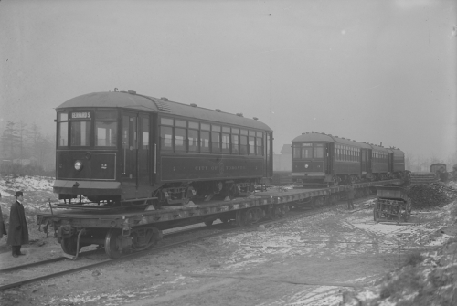Two streetcars sitting on top of an open train car.