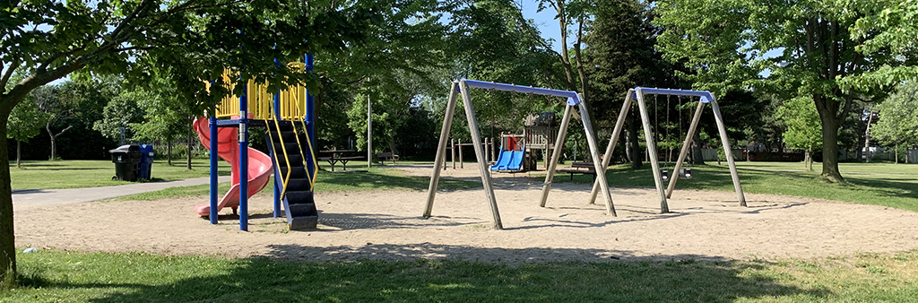 A photograph of Clydesdale Park Playground on a sunny day. The red spiral slide and swing sets are in the foreground, with the junior play structure in the background. The playground is surrounded by grass and mature trees.