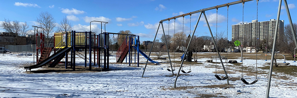 A photograph of Eastview Park Playground during the winter time. Four belt swings are in the foreground with a large play structure with slides and climbing options in the background. The playground is surrounded by a field with grass, mature trees and an apartment building in the distance.