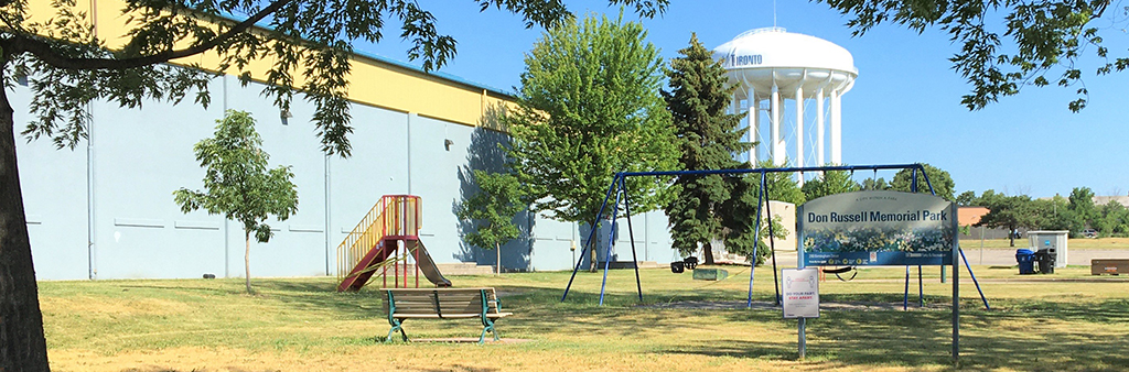 A photograph of Don Russell Memorial Park playground on a sunny day. The small playground is surrounded by grass and sparse trees with a water tower in the distance. The playground includes a swing set and small slide with stairs. There is a park sign, a bench and garbage and recycling bins.