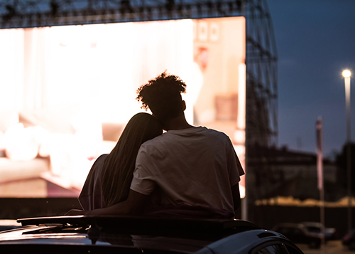 Image depicts male and female watching a movie at a drive in theatre.