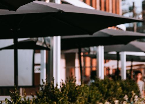 Image depicts umbrellas on street outside restaurant.