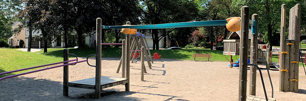 A photograph of Longwood Park Playground on a sunny day. The image focuses on the hand glider structure with platforms. Other features in the distance include a wood climbing structure, the swing set, see-saw and park bench. The playground is surrounded my grass and mature trees.