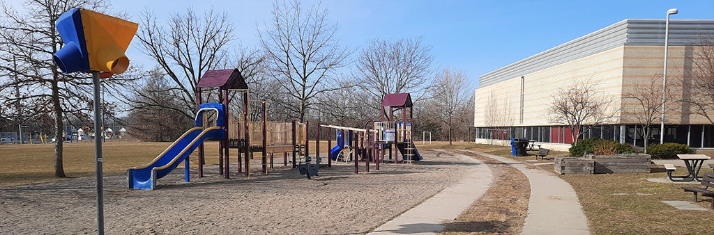A photograph of Ellesmere Park Playground, which is located beside the Ellesmere Community Centre (to the right in this photo). The playground has sand play surfacing and includes two small play structures. The playground is surrounded by a narrow concrete pathway on one side and an open grassy area on the other side.