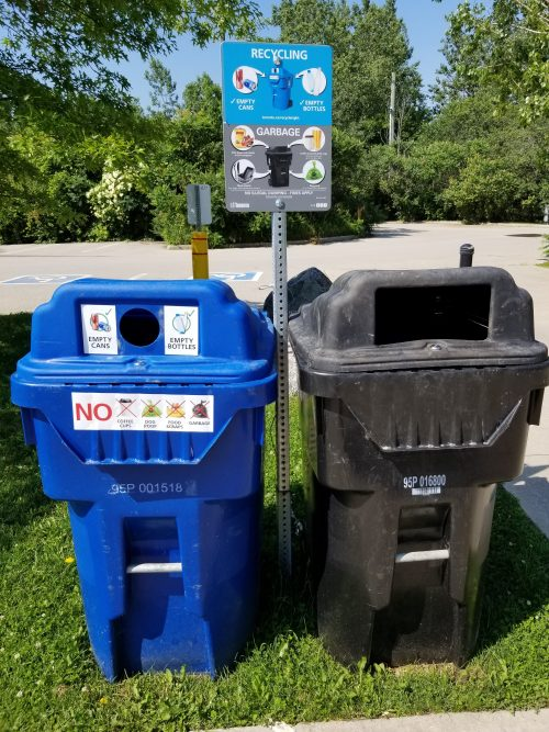 Beverage Bin with signage that reads Empty Cans and Empty Bottles beside a Garbage Bin