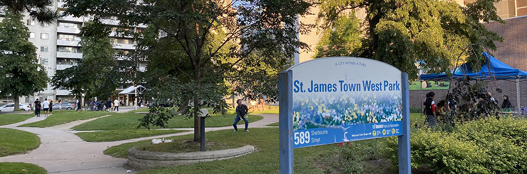 The image shows a view looking into St. James Town West Park from the west entrance on Sherbourne Street. The park's mature trees and pathways are shown.