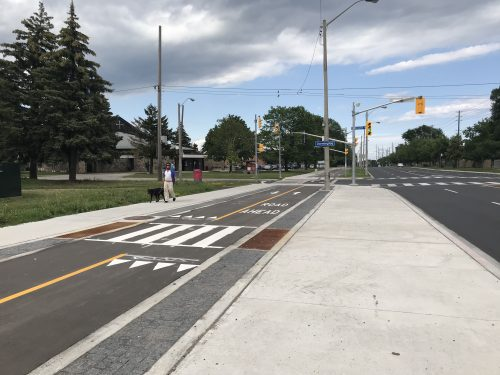 A multi-use trail is separated from motor vehicle traffic, and includes pavement markings and crossings for pedestrians.