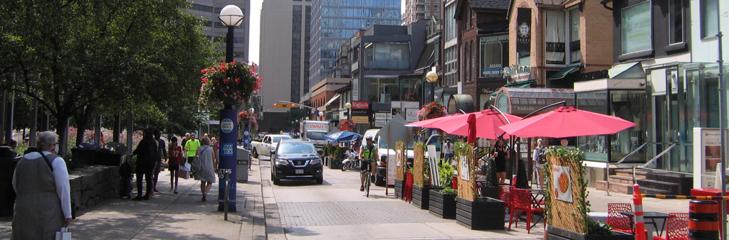 Cumberland Street in the Village of Yorkville, showing dining patios along the road and pedestrians walking next to a park
