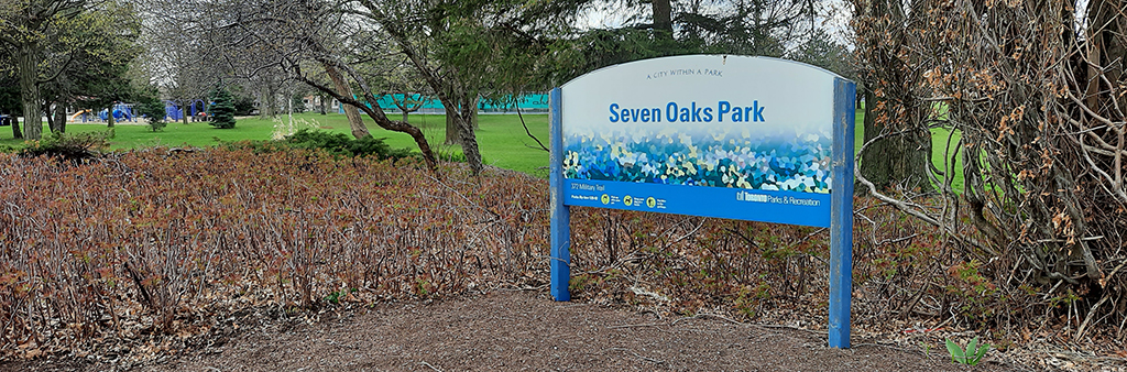 An image of the park sign at the entrance of Seven Oaks Park. Mature trees and plants surround the sign.