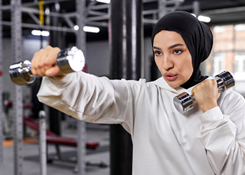 Young woman working out with weights in a fitness centre