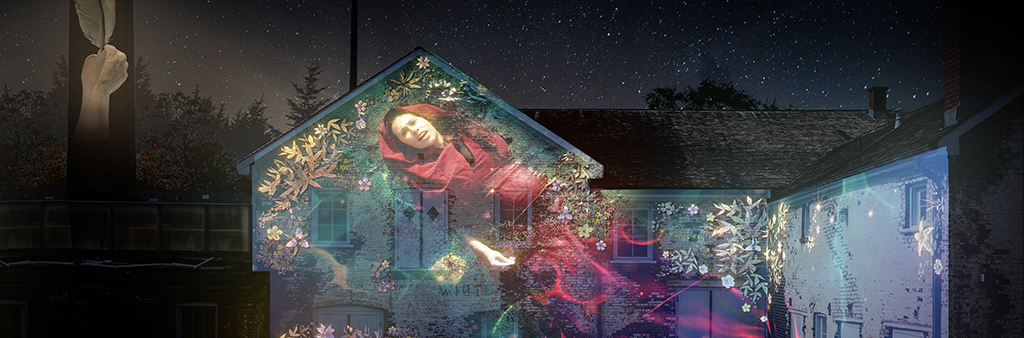 Light projections onto historic buildings of a hand holding a quill and a woman surrounded by flowers