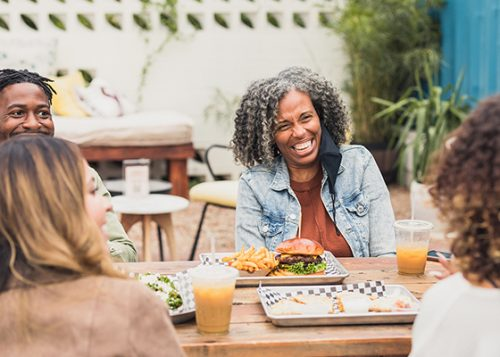 Friends laugh as they eat on a restaurant patio