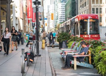 View of King Street with people sitting on the Muskoka chairs while a streetcar arrives at a stop with bicycle ring and post stands on the sidewalk