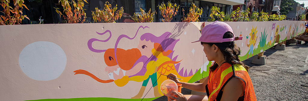 Person wearing an orange safety vest painting a colourful animal head on a streetfront construction hoarding.
