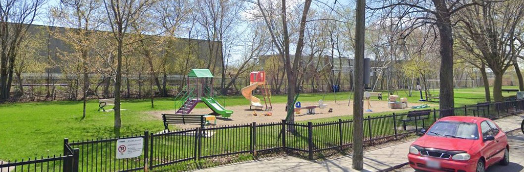 An image of Geary Avenue Parkette Playground taken from the road adjacent to the playground. A black fence encloses the playground, which includes various standalone play elements include two slides, a see-saw, swing sets and benches.